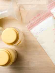 Pump parts beside two bags of breast milk