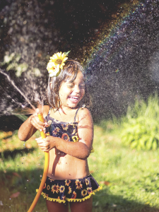 Image of girl playing with a hose in the backyard.