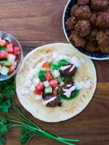 Falafel sandwich with bowls of falafel and tomato cucumber salad