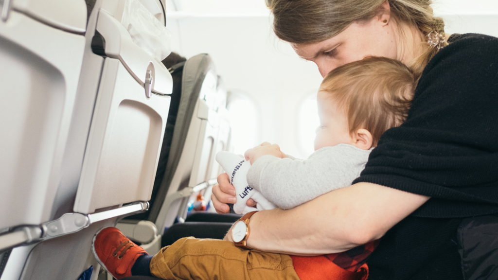 Mother holding her baby on a plane