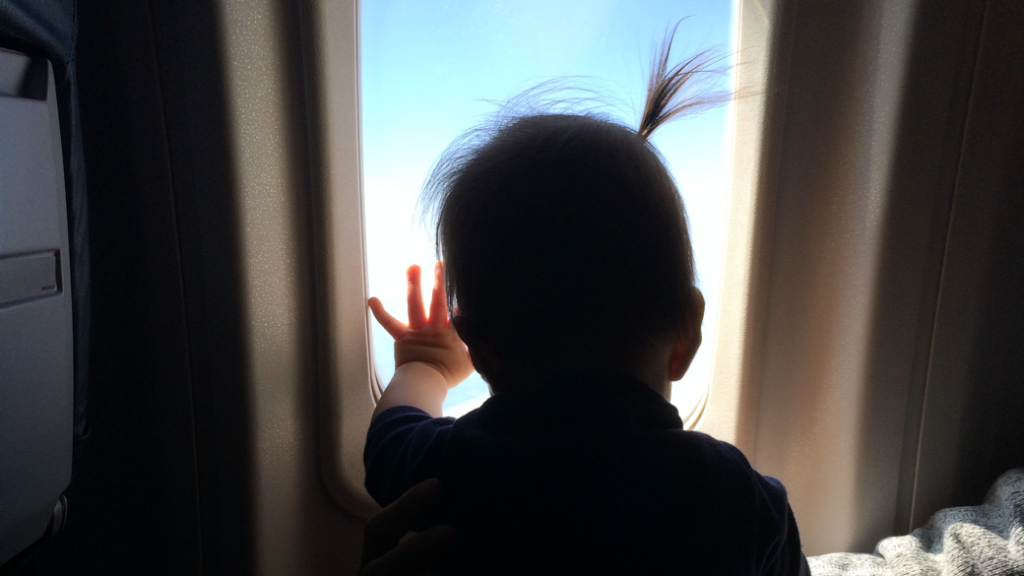 Baby looking out airplane window