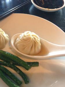 Xiao long bao in a soup spoon