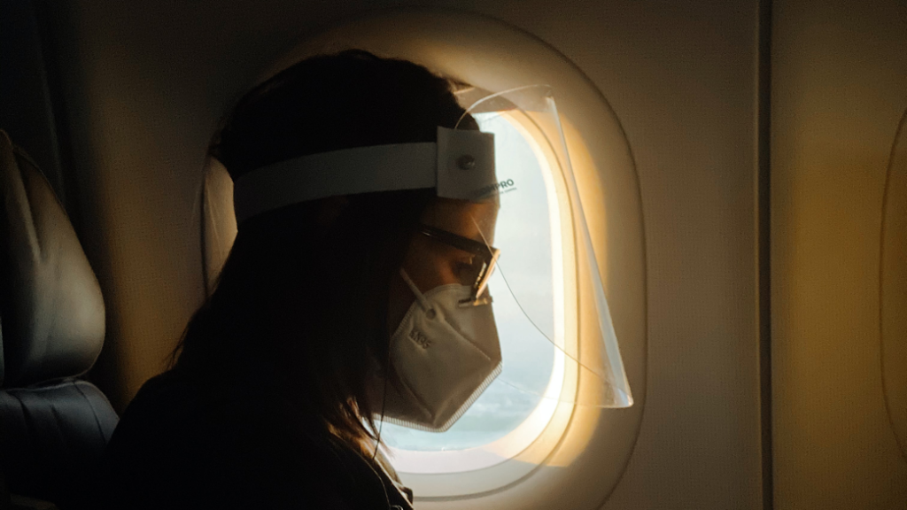 Woman wearing face mask on plane